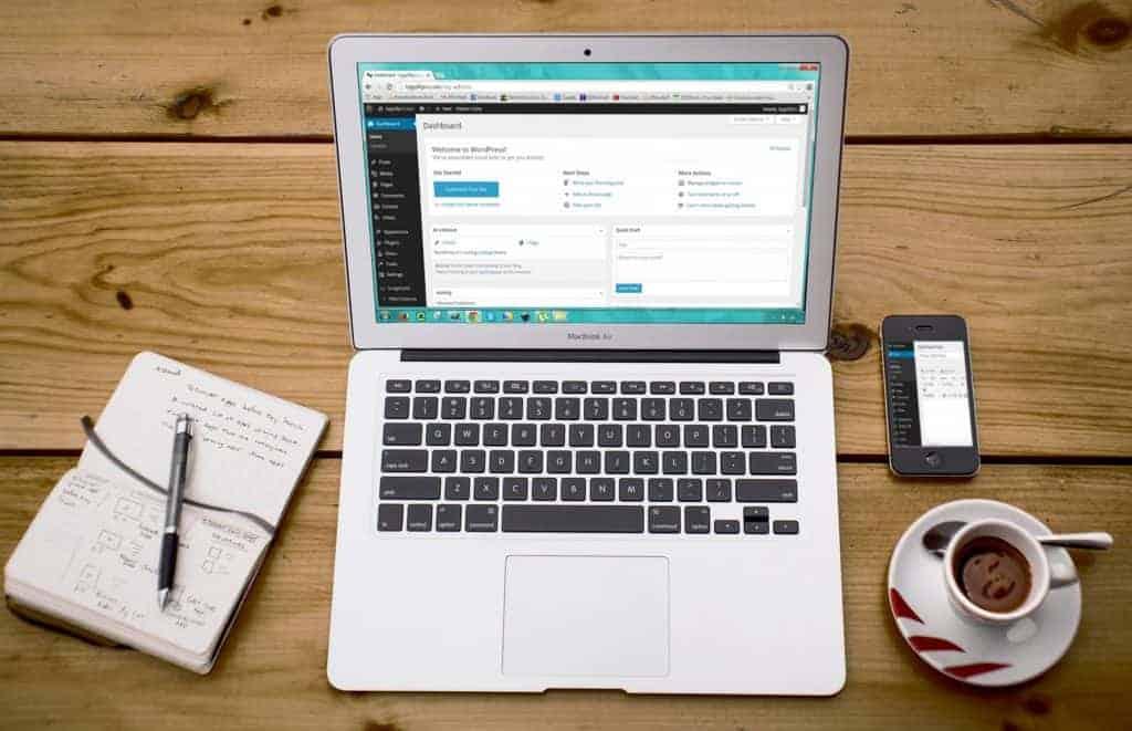 flatlay image of laptop, notebook, iphone and coffee mug